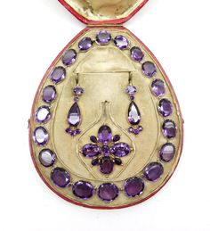 19th century amethyst and gold suite comprising a necklace, cross pendant-brooch and pair of earrings, English c.1840,  the necklace with graduated oval faceted stones, the uniform cross with an oval stone to each arm and smaller pear shaped stones between, the earrings formed of a pear shaped stone, triplet cluster below and oval stones, all open cut-down collet set in gold, contemporary case