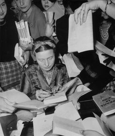 Simone de Beauvoir signing books.  Curious detail: on the right, someone asks her to autograph Troubled Sleep (in Portuguese) by her long term romantic partner Jean-Paul Sartre.