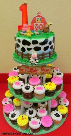 Farm cake with cow print round cake, barn topper and animal cupcakes
