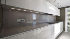 Cocina moderna, muebles lacados en blanco alto brillo con uñero integrado, encimera y aplacado en Dekton color topo, suelo color gris, papel Roberto Cavalli,
