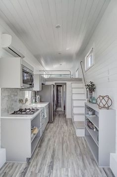 A white farmhouse sink, four burner cooktop, over the range microwave/venting hood, and full size refrigerator make the kitchen as functional as it is beautiful. house design Fox by Modern Tiny Living - Tiny Living Best Tiny House, Modern Tiny House, Tiny House Living, Tiny House Plans, Tiny House On Wheels, Living Room, Tiny House With Loft, Tiny House Kitchens, Tiny House Luxury