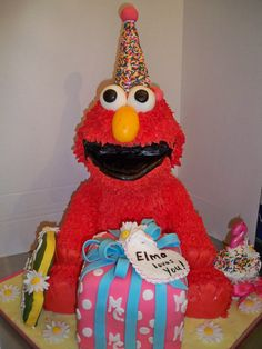 3D Elmo Birthday (all edible).  Elmo's head, legs, present, and cupcake are cake.  Elmo's head, arms, and sesame street birthday sign are krispy treats. For more views of Elmo, visit enchanted creations by melissa facebook page.