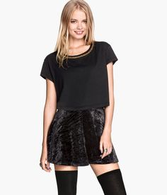 Short black crop top with decorative gold metal chain at neckline.│ H&M Divided