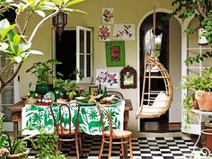 I love the black and white checked floor, the green otomi tablecloth, the hanging egg chair, and the mix of plants.  Amber Interior Design