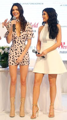 Kendall Jenner in a printed romper and Kylie Jenner in a white A-line mini dress