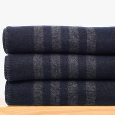 This luxurious cashmere blanket is knitted with multiple colored yarns into an original graphic stripe pattern. This heavy weight cashmere blanket adds visual texture when draped on the edge of your bed or draped over the couch. This new style has four contrast stripes at top and bottom edges adding a novel detail to our classic blankets. The reverse side is the same colors inverted in the opposite pattern with navy stripes on a heather grey background.Additional Information:• 100% Cas...