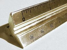 A triangular architect's scale, made of brass