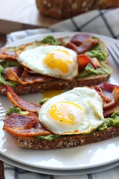 This open-faced breakfast sandwich is a quick and easy fix for mornings or brunch with chilled guacamole spread, crisp bacon and sunny side up eggs.