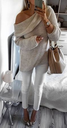Off the shoulder beige sweater with white jeans.