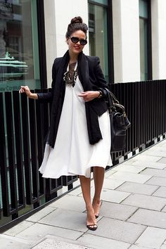 Coggles Fashion - London Street Style with knee length loose white dress, black tailored cropped blazer, black scarf, black oversized sunglasses, statement necklace, oversized bag and black sandals.