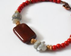 This Designs by s.e.K bracelet features dark red jasper surrounded by brushed brass, labradorite, and red jasper beads, closed with an antique copper-plated brass button clasp.