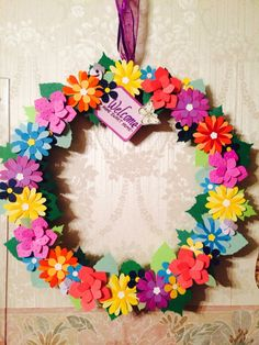 paper flowers. cut out with punches,glued together and glued onto a wooden hoop.