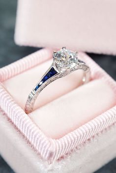This gorgeous engagement ring features a round brilliant cut diamond in a six prong setting at the top of a narrow white gold shank, accented with blue sapphires, diamonds, hand engraving, and milgrain beading. Designed and created by Joseph Jewelry Design Your Own Engagement Rings, Antique Engagement Rings, Diamond Engagement Rings, Yellow Gold Rings, Rose Gold, White Gold, Diamond Wedding Bands, Wedding Rings, Boho Wedding