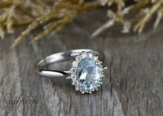 Oval Aquamarine Engagement Ring in 14k White Gold,Aquamarine Wedding Ring,8x6mm Oval Halo Moissanite BridalRing,March Birthstone by Sapheena This engagement ring is set with a high quality natural blue aquamarine oval cut center stone and surrounded by a halo of brilliant round cut