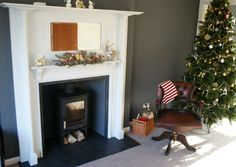 Charnwood C-FOUR on log store with honed granite hearth and slips, painted arts and craft surround.