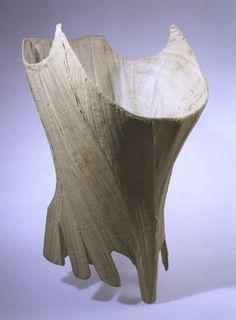 MatrizNet  Datação:    1660 d.C. - 1680 d.C.      Matéria:    Linho creme; fio de algodão creme; barbas de baleia; crina.      Dimensões (cm):    altura: 39 cm; largura: 73 cm;       Descrição:    Espartilho de linho creme pespontado a fio de algodão da mesma cor. Interior armado com barbas de baleia e crina. Corpo terminando em bico na frente. Aba golpeada. Aberto atrás com ilhós caseada. Forro de linho.