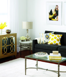 Glam charcoal textured sofa, given depth with geo gold, grey & back scatters and white side table.