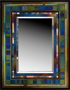 """""""Jazz II""""  Art Glass Mirror   Hand cut glass piece are precisely assembled to create exquisite glass mosaic. The iridescent glass changes color with lighting conditions. Some of the glass pieces are drawn on by the artist with a kiln fired vitreous paint to establish the character of each unique mirror frame. Can hang either vertically or horizontally. Signed on back. Dimensions refer to the overall size of the piece. Mirror size is 18""""H x 12""""W.  Dimensions: 28.5in H x 22.25in W x 1.5in D"""