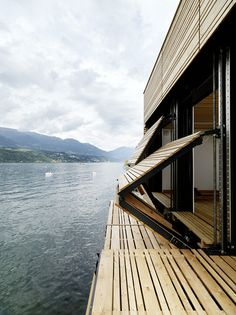 Siberian larch garage doors enable water access for boats and, on upper floors, allow breeze and light into the interior of a boathouse at Lake Millstatt.