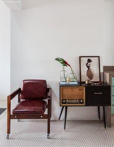 Piso em formato de colmeia e peças vintage como cadeira e rádio antigo.