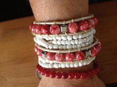 Een leuke combinatie van 3 armbanden. Armband met rode kralen en bedeltje €10.- elastische armband met witte kraaltjes (+\- 45cm) €10.- en de wit leren wrap (2x rond je pols) € 19,95
