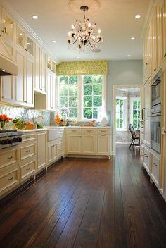 Cream cabinets, brass hardware, green arabesque tile backsplash, chandelier, hand scraped wood floor