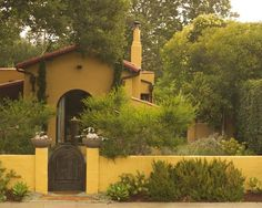 like the gate with stucco fence...the color of yellow is pretty too and placement of the landscape looks inviting