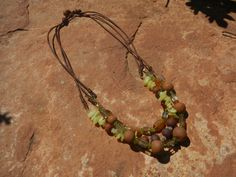hand made, high fired stone ware clay, semi-precious stones. Leather cord necklace