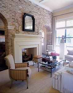 Exposed brick, floor to ceiling windows, and fireplace divider... sold! (Not sure about the decor though)