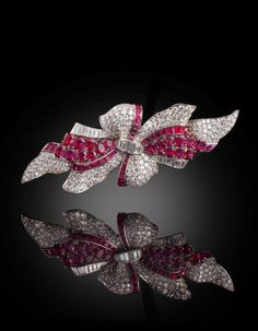 An art deco diamond and ruby double clip brooch, Trabert & Hoeffer-Mauboussin, circa 1935 each plaque designed as a pavé-set diamond bow, with baguette-cut diamond trim, enhanced by oval and calibré-cut rubies; signed Trabert & Hoeffer-Mauboussin, no. 3845; estimated total diamond weight: 14.50 carats; mounted in platinum; length: 4 1/4in.