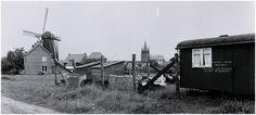 """Veldhoven, Zeelst, Hoogstraat gezien richting Korenmolen """"Zeelst"""", rechts daarvan de 'R.K. kerk H. Willibrordus' Foto Waarma (fotograaf) 1956"""