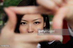ストックフォト : Young woman looking through fingers making a frame