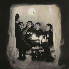 """'Children Singing in a Snow Cave'- Niigata Prefecture, 1956. Hamaya is quoted about the photo, he says, ""The village Toka-machi is famous for snow. On the night of the Lunar New Year, snow caves are made all over town. Children light candles, bring braziers, and have dinner inside. Adults are invited to be their guests. They sing bird-chasing songs to the beat of clappers. It's the children's kingdom all through the towns and villages."" …Is there anything more lovely than that?"""