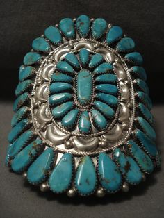 This is a tremendous vintage Navajo museum quality huge silver cluster bracelet. This colossal bracelet contains outstanding large teardrop shaped Number 8 turquoise stones. Circumscribing the center cluster are amazing repoussed shells and beads with accenting silver ropes. This bracelet includes a superior triple silver shank cuff. The height at the center of the piece measures around 3-7/8 while the width at the center of the cuff measures around 2-5/8. The center stone measures around…