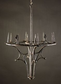 A Gothic Wrought Iron Chandelier: Wilkinson's Auctioneers, Doncaster, 25.11.2012, lot 87. £ 1'800. The central stem and hook supports the four tracery brackets. The eight spikes centring drip pans on a circular scalloped edge band. 26½ ins (67 cms) in height, 17½ ins (45 cms) diameter. I don't know how 'authentic' this is - I have never seen one contemporarily illustrated.