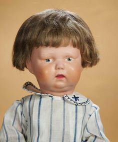 """All-wooden doll with very chubby face, double chin, decal/painted eyes, closed mouth with downcast pouting expression, original brunette mohair tacked on wig, spring-jointing at shoulders and elbows, hinge-jointed """"walking"""" legs, nicely costumed. Excellent condition, with virtually flawless original finish, original wig. Schoenhut, circa 1918"""