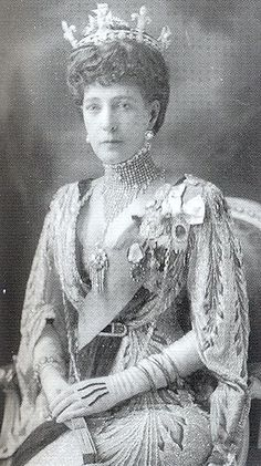 "Queen Alexandra, 1910. ""Queen Alexandra wears a Cartier necklace in 1910. She was famous for wearing high chokers in the style shown and for wearing a daring amount of make-up, in so doing rejecting the fashion for natural complexions."""