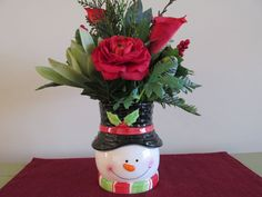 Snowman Christmas Arrangement, Red Rose and Calla Lilly, Red Berries, Green Succulents, Ferns, Evergreen Filler, all in a cute Snowman Container.