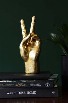 About The Gold Peace Hand OrnamentA gloriously iconic piece within the Rockett St George Collection, the Gold Peace Hand Ornament looks effortlessly stylish and absolutely fabulous when on display. We love a perfectly curated collection of ornaments and t Accessories Display, Living Room Accessories, Decorative Accessories, Home Accessories, Decorative Objects, Black And Gold Bathroom, Dark Green Walls, Pile Of Books, Rockett St George