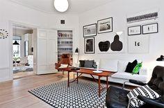 Salón bicolor, en blanco y negro, solo roto por la mesa y el sillón en marrón. #decoracion #salon