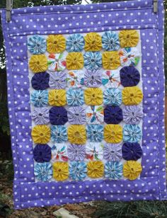 This is a handcrafted doll quilt made with 2 inch fabric yoyos.  Mixture of patterns and colors including yellow, purples, blues. Backed and bound with a purple with white polka dot fabric, cotton batting inside. Tied with light blue embroidery thread.  Measures 16 1/2 inches wide by 21 inches long.  Would be a cute security blanket for a small child.  Can also be used as home decor as a table mat, or can be used as a wall hanging if ribbon is attached.  Machine washable. Carefully craft...