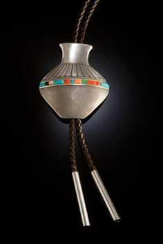 "Norbert Peshlakai (Navajo) Silver seed pot bolo tie, 2008, 3 1/8"" height, stampwork and hammered texture silverwork with stones including coral, jade, and shell, with wire fittings. Hallmark is artist's logo. Peshlakai was one of the first artists to make a silver seed pot around 1976. He excels in the art form and based this shape on one from the cover of the book Old Traditions in New Pots."