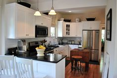I like the overall in this kitchen: subway tile backsplash, black counters, white cabinets, wood floors.