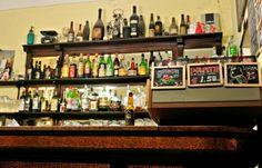 """Caffè Vini Emilio Ranzin, anche chiamato """"la piola delle acciughe"""", risale al 1848, prima della riqualificazione del Quadrilatero, quando ancora il nome era """"la piola dalle tende verdi"""" e una signora cucinava piatti della tradizione piemontese nel retro del locale."""