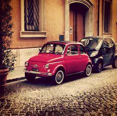 Un contraste doux entre une Fiat 500 rouge aux airs vintage et une Smart noire toute moderne. #Fiat500 vs #Mini