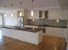 Dark stone benchtops on white cabinets with dark glass splashback sitting on similar to spotted gum floorboards