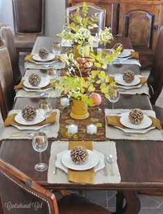Mom's Thanksgiving Table.  We linen napkins as placemats and a white plate set that picked up at Pier One a few years ago.  Mustard napkins and leaves in yellow rustic ceramic containers bring color, and for fun I added some decorative wood balls that look like shaved pinecones.