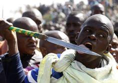 Marikana: A year on | A protester licks his spear.