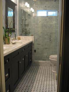 carrara white subway tiles in shower - black/white interwoven tile on floor - frameless glass door - black granite countertop and white cabinet - like the raised wall between vanity and shower
