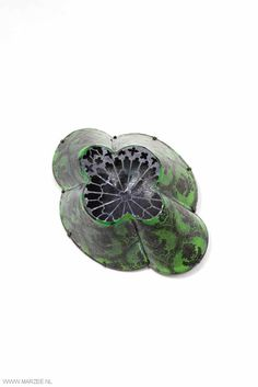 Vera Siemund, brooch, 2012, enamelled copper, steelsawn, mounted, enamelled (printed portrait/ornament) - 73 x 100 x 42 mm - green ornamented lamp shape covered with a fragment of a rose window, inside a photo portrait